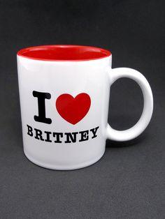 """Comemorando o aniversário de 33 anos de Britney Spears, disponibilizamos em nosso catálogo a caneca """"I Love Britney"""". Inspirada na campanha """"I Love NY"""" de 1977, a caneca retrata de forma simples o amor dos fãs pela Princesa do Pop!  Caneca bicolor (externo branco / interno vermelho) com arte impressa nos dois lados nas cores vermelho e preto."""