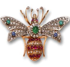 A gem-set and diamond brooch in the form of a bee with cabochon ruby and rose-cut diamond body, en tremblant wings of rose-cut diamonds accented with emeralds and sapphires, and completed by circular-cut ruby eyes; mounted in silver topped fourteen karat gold
