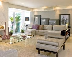 Sala em tons claros com sofa cinza e iluminação direta. Projeto de Fernanda Marques.jpg
