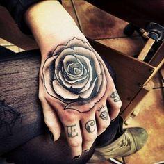 Una rosa de color negro tatuado sobre el DORSO DE LA MANO de una mujer. Usualmente se tatúan las flores de colores, pero existen interesantes excepciones ...