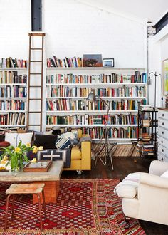 White room with white bookshelves, dark wood floors, red patterned rug, white chair, yellow couch, patterned pillows, silver floor lamp, and wood ladder
