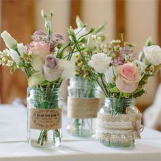 Beautiful pastel coloured flowers in jars decorated with twine
