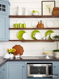 Rustic open shelves let a collection of white dishware and vintage wicker pieces take center stage. Just a few citrus green accents bring the perfect dose of color against a shiplap-siding backdrop. The inexpensive wall treatment carries cozy appeal and meshes well with beachy cottage kitchen design.