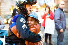 Devonte Hart and Sgt. Bret Barnum – a black boy and a white police sergeant – met at a Ferguson protest in Portland, Ore. The photo of them hugging has melted millions of hearts. Police Sergeant, Police Officer, Police Cars, Ferguson Protest, Michael Brown, Thing 1, Free Hugs, Adopting A Child, Firefighters