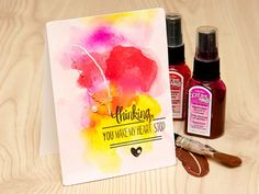 Today I have a very special card and video to share with you – I'm showing how to easily create a watercolour background with the help of spray inks.  In my video I'm using spray inks from ClearSnap (ColorBox spritzers) and Studio Calico. Both of these are waterbased non shimmer inks. I've also experimented a bit with ClearSnap Smooch spray inks and  Color Magic from Heidi Swapp – those sprays created a nice shimmer on my background.
