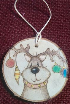 This Reindeer ornament was wood burned by hand onto a piece of reclaimed birchwood. I added watercolor paint and sealed it with a clear varnish.The size is approximately in diameter by deep.It has a hemp cord attached for hanging.I accept custom requests! Wood Slice Crafts, Wood Burning Crafts, Wood Burning Patterns, Wood Burning Art, Reindeer Ornaments, Painted Ornaments, Christmas Tree Ornaments, Christmas Plaques, Christmas Signs