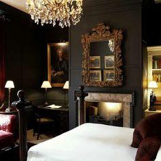 Dark walls, chandelier, fireplace, crisp linens