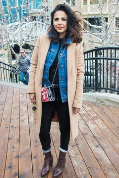 Azita Ghanizada wears a black t-shirt, denim jacket, beige coat, skinny  jeans, boots, and a crossbody bag