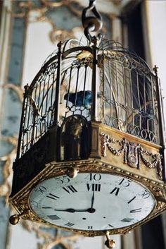 an antique birdcage with a lovely clock underneath. bronze detailing makes this very fabulous!! a beautiful piece.