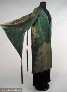 Scalloped inserts of reversed dotted sprays: emerald green silk satin against gold lamé & gold against green, vest-like cape w/ silk bound armhole, pagoda style over-sleeve w/ deco carved wood drops & long gold fringe, 1 hook & hand bound eyelet at centefront drop waist, intricate scalloped piecing, possibly Jeanne Lanvin,