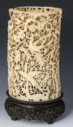 Chinese carved ivory reticulated brush pot, carved in relief with phoenix motif, with wooden base. Size: 11 x Century