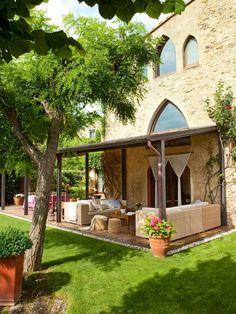 Los sofás de exterior son de la firma Dedon y se equipan con cojines, de Cul de Sac. Los pufs de fibra natural son de Jordi Batlle. Las ventanas ojivales facilitan que el paisaje ampurdanés se cuele en la casa.