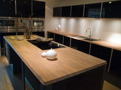Trendy kitchen high gloss black cabinets with wood butcher block counter