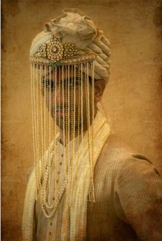 A rustic yet modern pearl sehra fit for a royal groom - love the pugdi and his regal gold kurta - Indian groom fashion - modern Indian groom - groom getting ready - wedding day photo shoot - portrait - moti sehra - sepia #thecrimsonbride