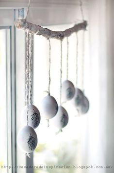Österliches Mobile in Naturtönen: Ausgeblasene weisse Eier als Osterdekoration von einem geweisselten Ast abhängen