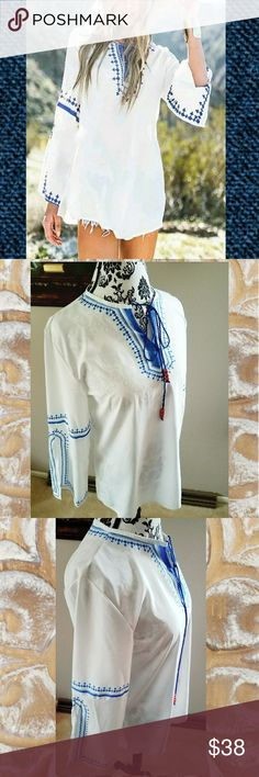 🆕WANDERLUST BOHO TOP Celebrate your free spirit in this beautiful long line embroidery printed top. Crisp white contrasted with bright blue geometric print. V-neck with tassel ties decorated with red wood beads. Long flare sleeve with deep cut slit that beautifully drapes over the arm. Light  and silky polyester fabric. Tops