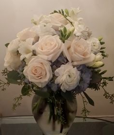 The bride bouquet features white ranunculus, white freesia, blue hydrangeas, and white roses.
