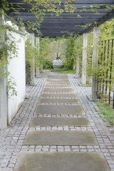 Paving and granite setts lead under a pergola to a large olive jar planted with something spikey - Astelia chathamica would be a good choice. If you planted this in a pot and then balanced it inside the rim of the urn you would be able to remove it if needs be ...
