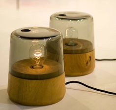 The Boya table lamp by Outofstock Design features a solid wood based made of either reclaimed oak or reclaimed maple, and a sheer lampshade of grey-tinted blown glass.    Marine-Inspired Table Lamps Resemble Fireflies Caught in a Jar
