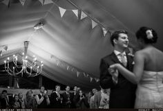 Black and white photo of wedding guests taking photos of a bride and groom having their first dance in a marquee at River Cottage in Dorset. The room is decorated with contemporary modern silver chandeliers and vintage print and striped bunting