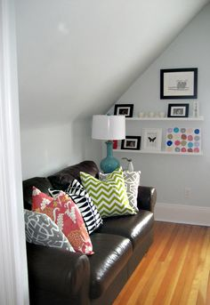 Colourful cushions against dark sofa; shelf space with hooks for walkway to door