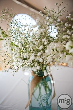 Maybe substitute daisies???? babys breath in a pink mason jar for a girl baby shower! Pretty!! Burlap ribbon around the neck of the jar.