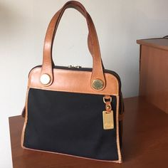 """Vintage Dooney & Bourke Cabriolet Carpet Bag Vintage Dooney & Bourke Cabriolet Carpet Bag, in good vintage condition with some light water marks on bottom and wearing on bottom corner as shown in last photo. Black canvas and interior are in near mint condition.  L - 10"""" W - 4 3/4"""" H - 9 1/2"""" Dooney & Bourke Bags Shoulder Bags"""