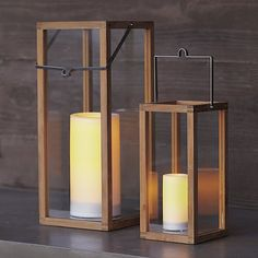Clean-lined lanterns cast a warm glow in the home or on the patio framed in unfinished teak and topped with a notched square stainless steel handle.