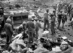 A wounded U.S. Marine soldier, lying on stretcher at left, is given blood plasma by American Navy hospital corpsmen on Iwo Jima, Japan, on March 3, 1945 during World War II.  Two Marines can be seen walking away, at right, after getting medical attention.  The aid station is surrounded by captured Japanese equipment.  (AP Photo/Joe Rosenthal) #