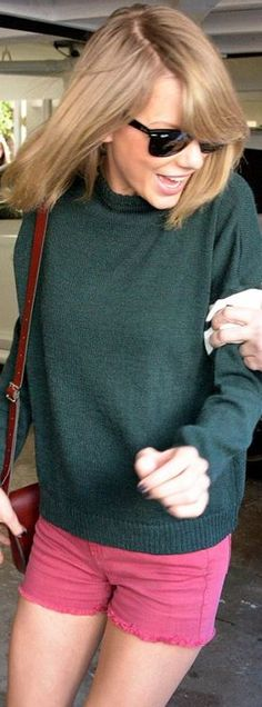 Who made  Taylor Swift's black sunglasses, red handbag, green sweater, and brown ankle boots?