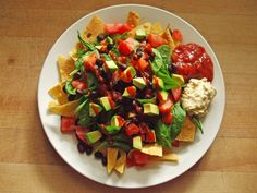 tortilla chips, seasoned black beans, spinach, tomato, avocado, sriracha, salsa, and hummus