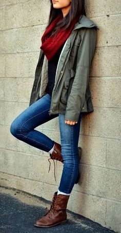 Army jacket, red scarf, casual tee and blue jeans with legit boots.