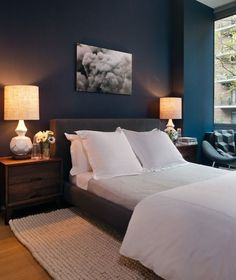 Suzie: Haus Interior - Blue bedroom with peacock blue teal walls paint color, charcoal gray modern platform bed, crisp white duvet & shams, natural woven rug, contemporary coffee stained wood nightstands and West Elm Terracotta Lamps.