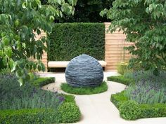 Textural slate sphere water feature with fabulous simple planting.  I like the planting around the base of the water feature.