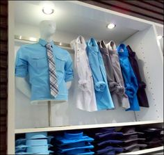 """Saddle-mount Bar Hooks thread through a sleeve and yank one arm back into a Half Nelson wrestling hold to coerce these shirts into display posture. I see visual merchandising like this often with Jeans, less so with retailing shirts. Maybe someone was transferred in from """"Slacks?"""""""