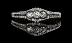 AN ART DECO SAPPHIRE AND DIAMOND BRACELET, BY J. E. CALDWELL Centering upon a geometric panel, set with three old European-cut diamonds within calibré-cut sapphires, mounted in platinum and 18K gold.… - Fine Art Auctions Miami - 02/12/2014