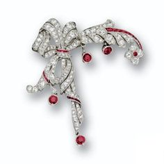 DIAMOND AND RUBY BROOCH, CIRCA 1920 Designed as a flowering branch held by a ribbon bow with a long articulated end, set throughout with small old European-cut and single-cut diamonds weighing approximately 3.00 carats, enhanced with small calibré-cut rubies and 4 collet-set round ruby pendants, mounted in platinum.