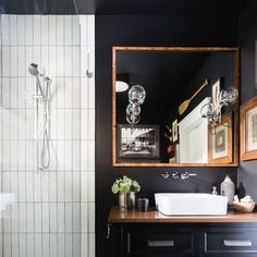 "40-square-foot bath. A larger, storage-friendly vanity with a Cambria countertop and Brizo faucet. The shower tile lies in a vertical-stack pattern, echoing the pinstripe detail on the bedroom wall. ""It also takes the eye up, making the ceiling feel taller,"" the designer says. A window was added to increase natural light; another light source comes from a pair of sconces from Schoolhouse Electric. The Surrey paint color was applied in a matte finish, but gloss finish by vanity."