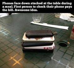 Phones stacked @ the table during a meal. 1st person 2check their phone pays the bill.