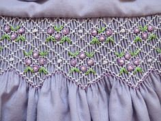 This lovely little lavender dress features delicate white smocking with gorgeous white and lavender clusters of rose buds and green leaves. The dress also has white peter pan collars edged with coordinating lavender piping and adorable short puffy sleeves with narrow cuffs. A beautiful sash ties into a sweet bow in the back and tiny white buttons fasten it up. The generous hem is sewn with a hem stitch and edges are finished with a french seam. The entire dress is made with utmost quality…