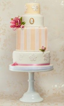 Beatrice is a five tier vintage wedding cake. Standing tall and elegant on four levels, Beatrice is stylishly decorated with  hand made pink tree peonies, a cameo,  pearls and ribbon.