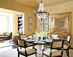 An antique French chandelier dominates this gorgeous dining room, off of which sits a sunny library - Traditional Home® / Photo: Werner Straube / Design: Eva Quateman