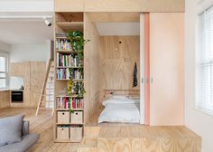 """one-bedroom apartment where a timber box and a mezzanine platform have been inserted to create three extra sleeping spots, without losing any living space"""