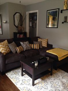 Grey and yellow living room with dark couch possible chocolate color and mix of taupe
