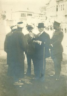 Gazi Mustafa Kemal İsmet İnönü birlikte köy hocaları ile yeni TÜRK, alfabesi üzerine görüşme yapıyor, Yanında yaveri Rusuhi bey de var. Fransız gazeteci tarafından bu resim Hacı bayram veli camisinin bir kaç metre önünde çekilmiş nadir bir görsel.  Ulus/Ankara 1928