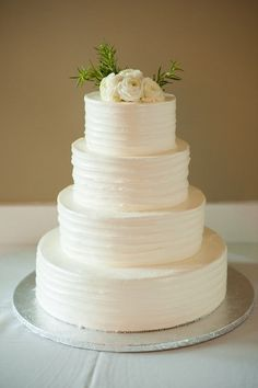 Classic white wedding cake idea - four-tier white wedding cake with textured frosting and fresh white ranunculus + greenery cake topper {Emma Cleary Photography}