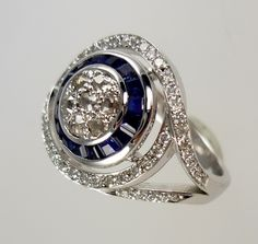 Platinum cocktail dress ring, set with sapphire and diamonds, which were taken from an old, unworn ring and redesigned to form a tapered circle