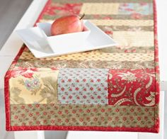 """Highlight 5"""" charm squares between 2-1⁄2""""-wide fabric strips in aquilt-as-you-go table runner to make home decor in no time. Table Runner And Placemats, Table Runner Pattern, Quilted Table Runners, Table Runner Tutorial, Quilting Tutorials, Quilting Projects, Quilting Ideas, Table Runner Christmas, Christmas Tables"""