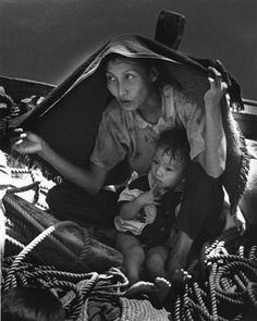 Eddie Adams, 'Vietnamese woman uses a blanket to shelter herself and her child from the hot sun aboard a refugee boat in Nov. 1977'