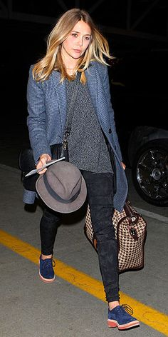 ELIZABETH OLSEN  Quite the blues traveler at LAX, the red carpet beauty dons a slate checked coat over Sinclair jeggings and navy buck shoes, adding a fedora for fun.